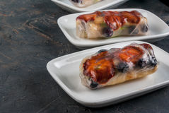 Sweet spring rolls with fruits and berries. On the black stone table, close view, copy space royalty free stock photography