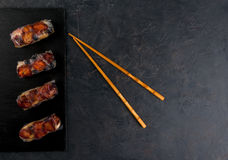 Sweet spring rolls with fruits and berries. On the black stone table, next to chopsticks for sushi, top view, copy space royalty free stock photography