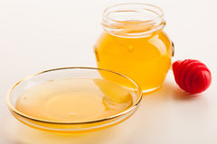 Sweet sticky golden fluid on transparent plate next to glass jar Royalty Free Stock Photo