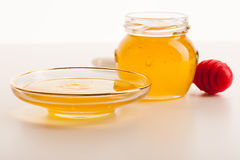 Sweet sticky golden fluid on transparent plate next to glass jar Royalty Free Stock Image