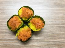 Sweet sticky rice with Egg custard and Sweet Coconut topping, wrapped in banana leaf. Popular Thai Dessert. Royalty Free Stock Image
