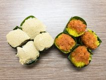 Sweet sticky rice with Egg custard and Sweet Coconut topping, wrapped in banana leaf. Popular Thai Dessert. Stock Photo