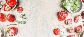 Sweet strawberries  with  powdered sugar  and mint leaves  on white shabby chic wooden background Royalty Free Stock Images