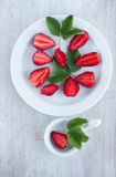 Sweet strawberry and green leafs on the white china dishes Royalty Free Stock Photo