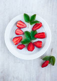 Sweet strawberry and green leafs on the white china plate Stock Photography