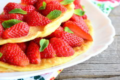 Sweet strawberry omelet. Delicious omelet stuffed with strawberries and garnished with mint on a plate. Fresh strawberries. Recipes for kids. Healthy omelette royalty free stock photo