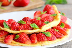 Sweet strawberry omelette. Delicious omelette stuffed with strawberries and garnished with mint leaves on a plate. Recipes for kids. Healthy omelette. Kids royalty free stock images
