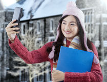 Sweet student with winter clothes taking picture Stock Image