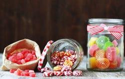 Candies. Sweet sugar candies in glass jars on brown vintage wooden background Stock Images