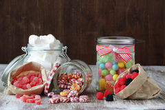 Candies. Sweet sugar candies in glass jars on brown vintage wooden background Royalty Free Stock Photos