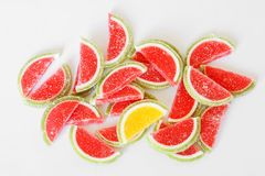 Sweet sugar marmalade in the form of slices of watermelon and lime lies on the white surface of the store counter stock image