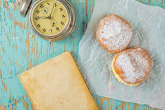 Sweet sugary donuts, book and vintage clock on rustic table Stock Photo