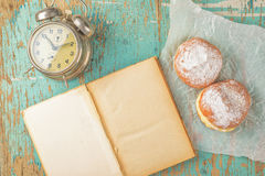 Sweet sugary donuts, book and vintage clock on rustic table Stock Images