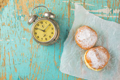 Sweet sugary donuts and vintage clock on rustic table Stock Images
