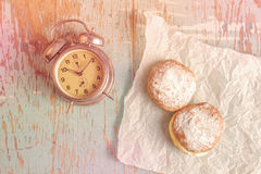 Sweet sugary donuts and vintage clock on rustic table Stock Photo