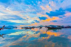 Chalong bay very important for travel business it is a center for all boat and yacht marina. Sweet sunrise above fishing boats in Rawai sea during high tide Stock Images