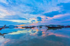 Chalong bay very important for travel business it is a center for all boat and yacht marina. Sweet sunrise above fishing boats in Rawai sea during high tide Stock Image