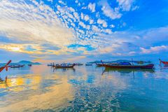 Chalong bay very important for travel business it is a center for all boat and yacht marina. Sweet sunrise above fishing boats in Rawai sea during high tide Stock Photo