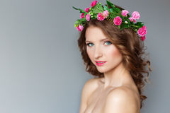 Sweet sweet beautiful sexy young girl with a wreath of flowers on her head, with bare shoulders with beauty makeup soft pink lips. A cute look at the  camera Stock Images