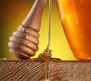 Sweet, sweet honey. Wooden stick with honey drops on it is near the pot of honey; honey stream flowing on a wooden table stock photography