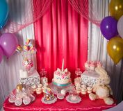 Sweet table and big unicorn cake for baby girl first birthday. Candy bar with a lot of different candies and sweet cakes.  royalty free stock images