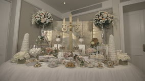 Sweet table with treats for guests. Details of the wedding, catering, Candy bar, bride and groom's suit. Flat video, S-log2 gamma stock video
