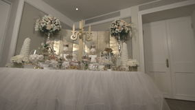 Sweet table with treats for meeting guests. Details of the wedding, catering, Candy bar, bride and groom's suit. Flat video, S-log2 gamma stock footage
