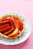 Sweet tart with peach on a plate Stock Images