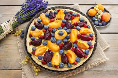 Sweet tart with peaches, plums and blueberries Stock Photos