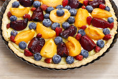 Sweet tart with peaches, plums and blueberries Royalty Free Stock Image