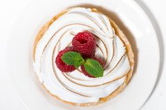 Sweet tartlet with meringue and raspberry on white plate. Top view horizontal Royalty Free Stock Image