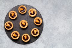 Sweet tartlets with chocolate and slices of tangerine on a dish of natural slate for serving, top view royalty free stock photo