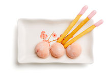 The sweet taste of Japan. Beautiful and delicious japanese mochi rice cakes and biscuit cookie sticks with pink friut cream on a rectangular dish isolated on Stock Photo