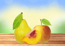 Sweet tasty apple, peach and pear on wooden table over nature ba Royalty Free Stock Images