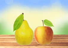 Sweet tasty apple and pear on wooden table over nature backgroun Royalty Free Stock Photography