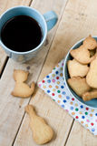 Sweet tasty cookies in the blue plate and cup of black coffee. On the wooden unpainted background Royalty Free Stock Images