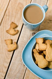 Sweet tasty cookies in the blue plate, a cup of coffee with milk Royalty Free Stock Images