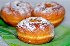 Sweet tasty donuts sprinkled with powdered sugar lie on a green glass plate, the national dish for the holiday of Hanukkah royalty free stock photo