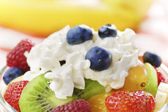 Sweet tasty fruit salad in the bowl with whipped cream Royalty Free Stock Photo