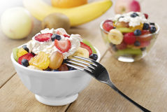 Sweet tasty fruit salad in the bowl with whipped cream Royalty Free Stock Photos