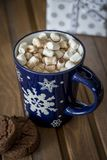 Sweet hot chocolate with marshmallows in cup at wood background stock images