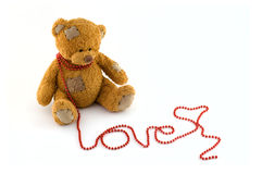 Sweet teddy bear with a string of red beads. Arranged in the word love on an isolated white background Royalty Free Stock Images