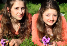 Sweet Teen BFF. Two pretty teen girls with long brown hair, lounging in the grass hanging out together with thoughts in their heads. Shallow depth of field Royalty Free Stock Photos