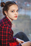 Sweet teen girl with tuft of hair. Portrait of a young girl with a tuft of hair in a red plaid shirt Stock Image
