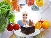 Sweet Temptation. Young woman stops her diet and look for a cake in the refrigerator Royalty Free Stock Photos