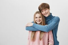 Sweet tender indoor shot of happy student couple hugging and cuddling against gray studio wall: fashionable guy in blue. Sweater holding tight his charming Royalty Free Stock Image