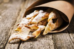 Sweet thin crispy cookies `Brushwood` deep fried topped with powdered sugar in paper bags Stock Photo