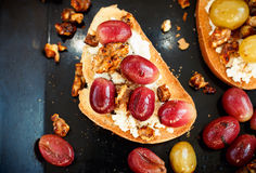 Sweet toast with red grape, ricotta, walnut on black baking Stock Photography