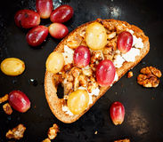 Sweet toast with red and white grape, ricotta, walnut. One sweet toast with red and white grape, ricotta and walnut on black baking Stock Photos