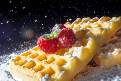 Sweet toast waffles with raspberries and a sprig of mint leaves and sifting pouring sugar powder in the sunlight close-up. Macro on a black background Royalty Free Stock Photo